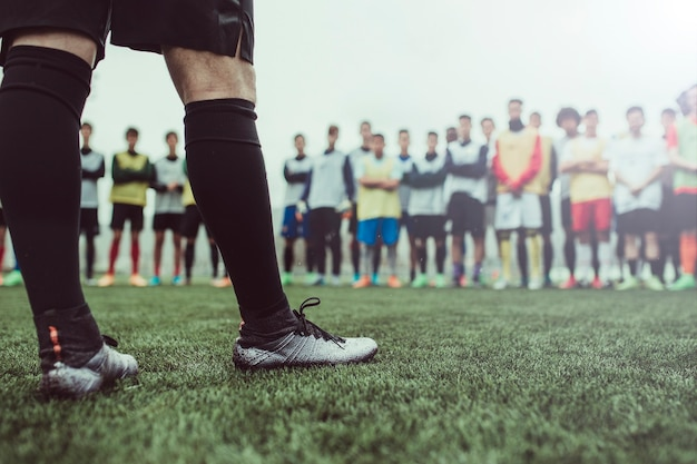 Деталь ног футболиста против группы мальчиков. он в шортах и носках. они находятся на зеленом футбольном поле. тренировка мужской команды в туманное утро