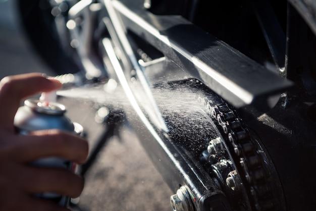 오토바이 체인에 스프레이 윤활유를 바르는 손의 세부 사항. 튀는 기름 방울의 근접 사진입니다.