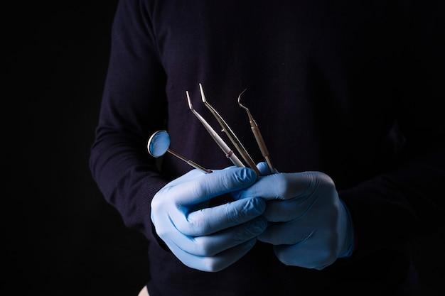 치과에서 치과 도구를 들고 손의 세부 사항. 치과 진료소.