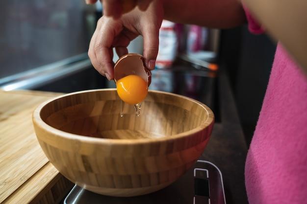 キッチンの木製ボウルの中で卵を割るピンクのセーターを着た女性の手の詳細