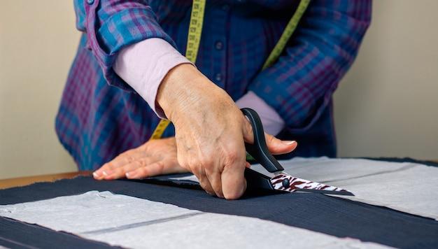 Деталь рук портнихи, разрезающей ткань, чтобы сделать одежду