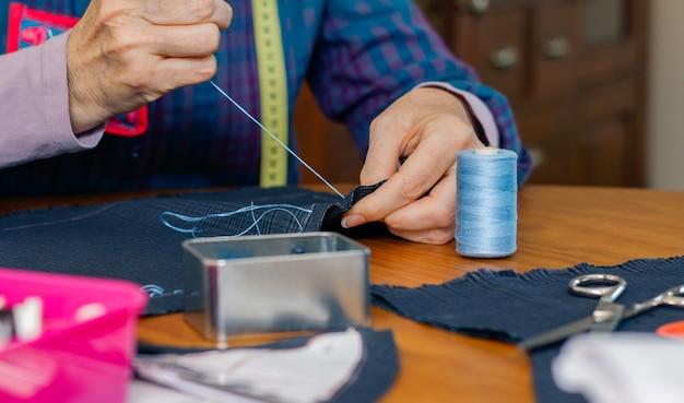 彼女のワークショップで衣服を作るために布を縫う年配の女性の縫い目の手の詳細