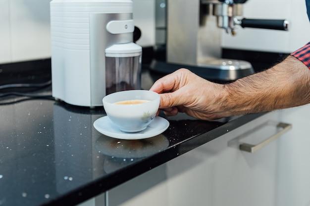 Деталь мужских рук, держащих чашку с кофе эспрессо