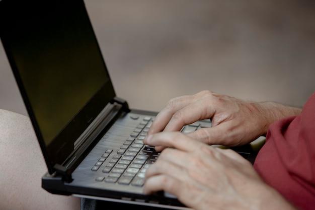 公園でノートパソコンのキーボードの男の手の詳細