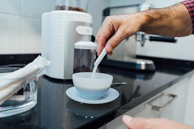 Деталь мужских рук, наливающих сахар в чашку с кофе эспрессо