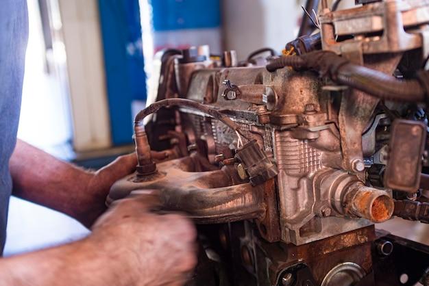整備士がワークショップで車のエンジンをオーバーホールする詳細