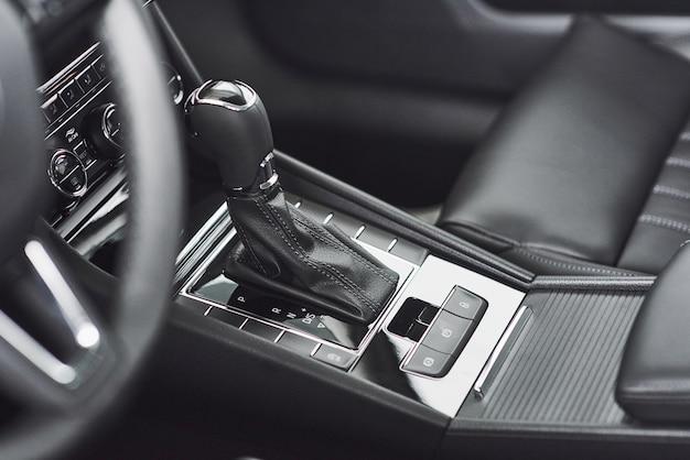 Деталь интерьера современного автомобиля, рычаг переключения передач, автоматическая коробка передач в дорогом автомобиле.
