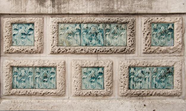 石の壁の長方形に刻まれたモダニズムの花の詳細