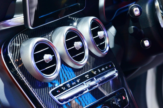 Деталь интерьера нового современного автомобиля, фокус на кондиционере.