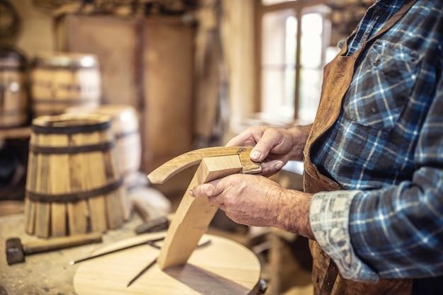 나무 통 조립을 위한 부품을 모으는 노인의 손의 세부 사항.