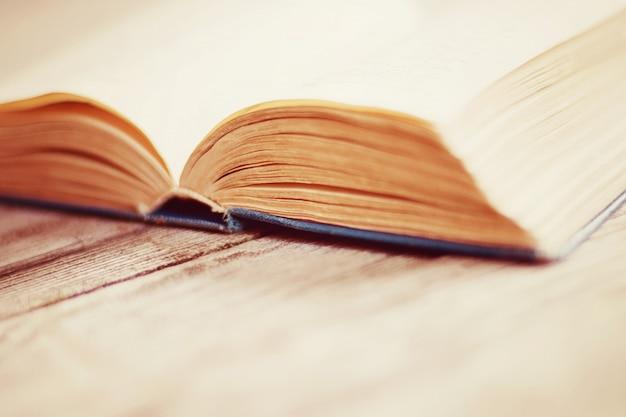 木製のテーブルに古い開いた紙の本の詳細