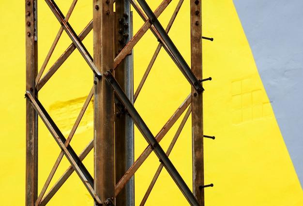 노란색과 회색 배경에 오래 된 녹슨 금속 다리의 세부 사항