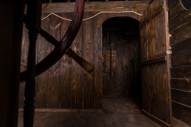 골동품 목조 범선의 오두막 및 내부 거실로 이어지는 열린 문의 세부 사항