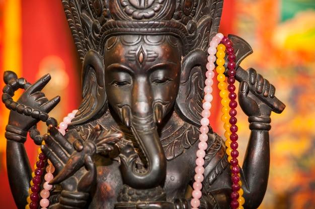 Деталь статуи восточной культуры, украшенной цветными ожерельями.