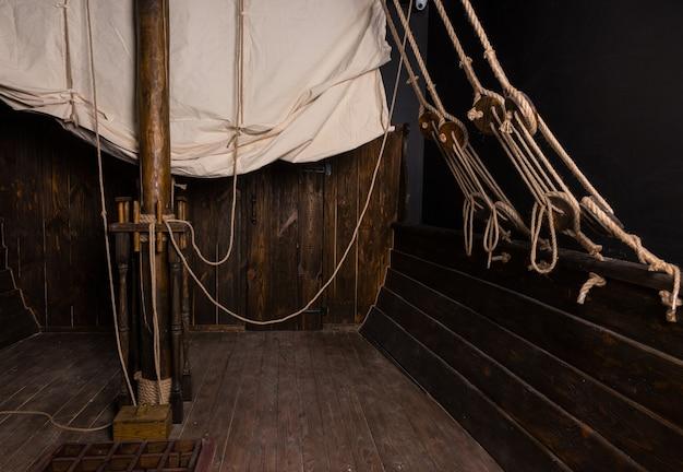 Деталь канатов и такелажа, прикрепленных к главной парусной мачте на палубе старинного деревянного парусного корабля