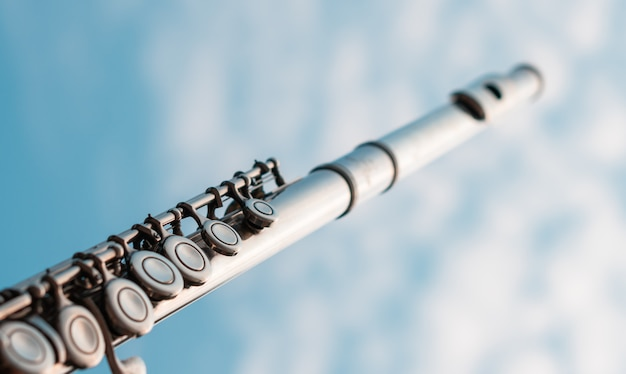 Деталь серебряной флейты ключ сияет закат светом с пасмурным голубым небом