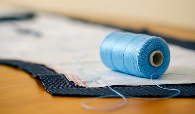 Деталь катушки ниток на ткани с выкройкой в швейной мастерской
