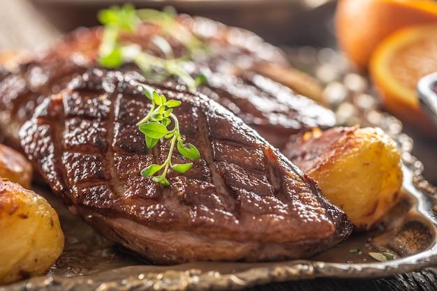 Деталь вкусных жареных утиных грудок и картофеля на старинной тарелке.