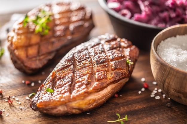 Деталь вкусных жареных утиных грудок и тушеной красной капусты на деревянной разделочной доске.
