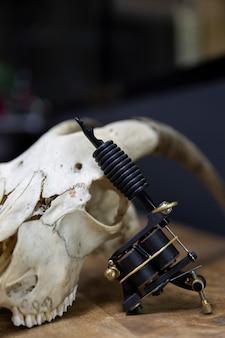 タトゥースタジオのヤギの頭蓋骨でサポートされているタトゥーマシンの詳細。テキスト用のスペース。