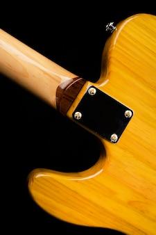 Деталь задней части шейного сочленения к корпусу желтой электрогитары.