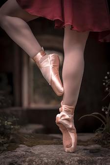 つま先で踊るバレエシューズを持つ少女の足の詳細