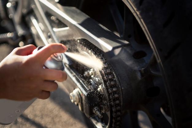 오토바이 사슬을 청소하고 기름을 바르는 자전거 타는 여성의 손의 세부 사항. 오토바이 관리 및 유지 보수 개념입니다.