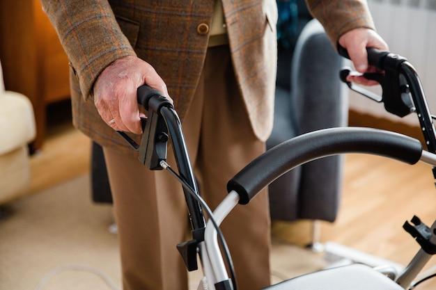 Деталь руки пожилого мужчины, использующего ходунки для обхода дома.
