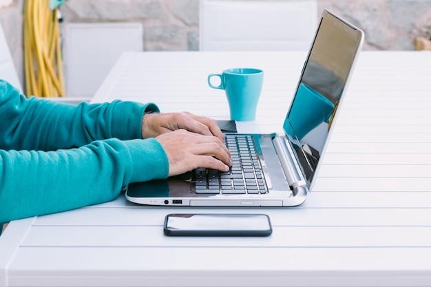 Деталь рук человека, телеработающего со своим ноутбуком, печатающего на клавиатуре, в саду своего дома
