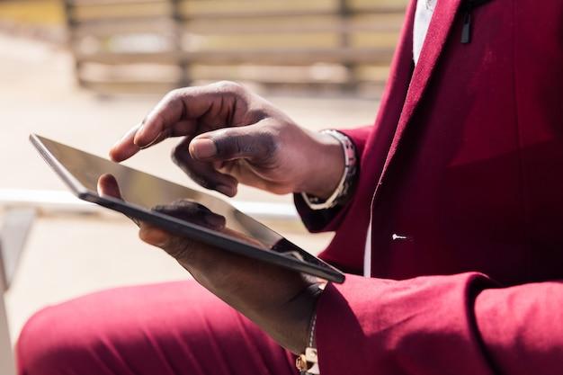 도시에서 야외에서 태블릿을 사용하는 아프리카 남자의 손에 대한 세부 사항,