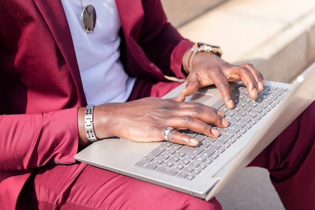 도시의 계단에 앉아 노트북 컴퓨터로 작업하는 알아볼 수 없는 아프리카 남성의 손, 기술 개념 및 원격 작업