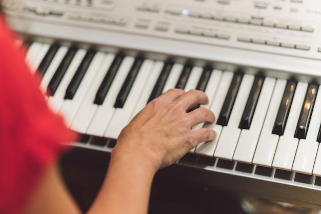 전자 피아노를 연주하는 여자의 손의 세부 사항