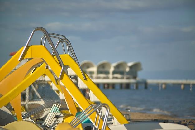 ぼやけたビーチの背景で、海辺のリゾートで観光客のために借りたいくつかのペダルボートのスクープの詳細。
