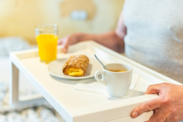 男性が持っている朝食付きトレイの詳細。高品質の写真
