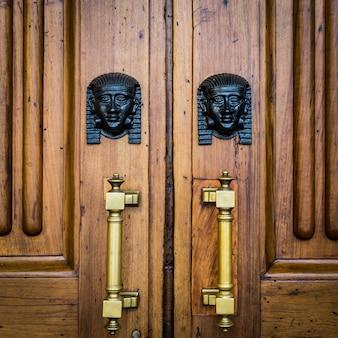 古い木製のドアにある2つのブロンズスフィンクスヘッドの詳細-約100年前、北イタリアのイタリアの宮殿