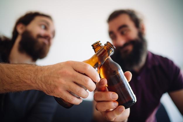 Деталь двух близких и улыбающихся друзей, разбивающих свои пивные бутылки