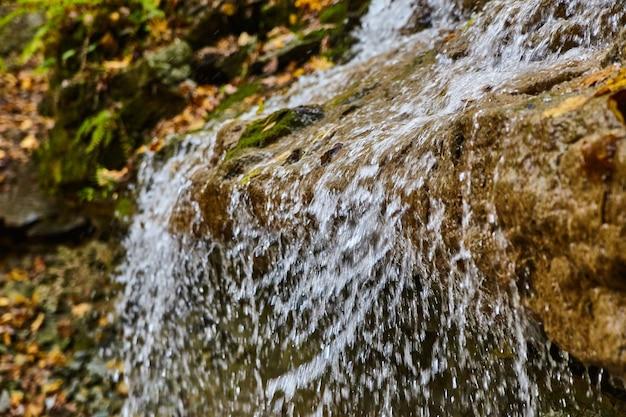흐릿한 가장자리 위로 흐르는 폭포 물의 세부 사항