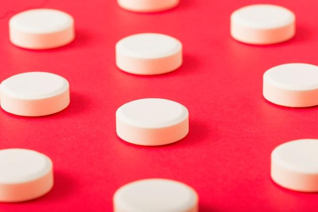Деталь белые круглые таблетки на красном фоне