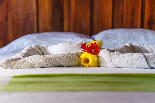 Деталь белых полотенец на кровати в номере горного отеля с украшением над ним.