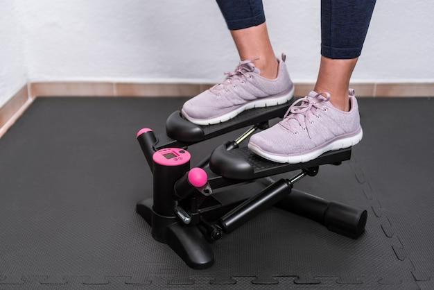 집에서 계단 등산 스테퍼 기계에 여자의 피트의 세부 사항. 격리 중 훈련의 개념.