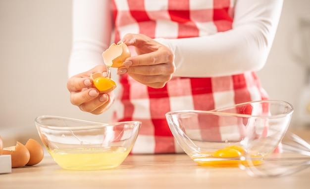 흰자에서 달걀 노른자를 두 개의 유리 그릇으로 분리하는 여성의 손의 세부 사항.
