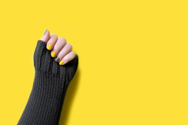 노란색과 궁극의 회색 매니큐어 손톱을 비추는 트렌디한 색상의 회색 스웨터를 입은 여자 손의 세부 사항