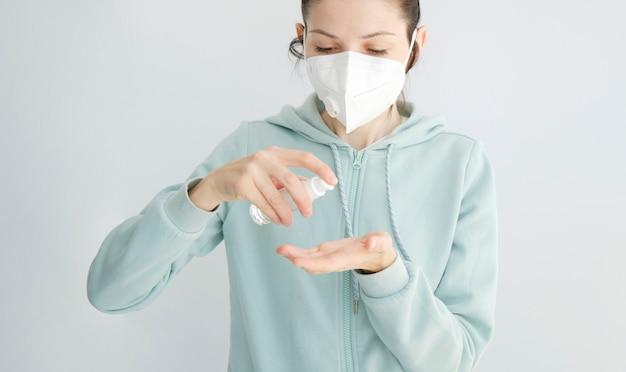 液体ゲル消毒を使用して、手をきれいにする若い女性の詳細。 covid-19ホームプロテクション。