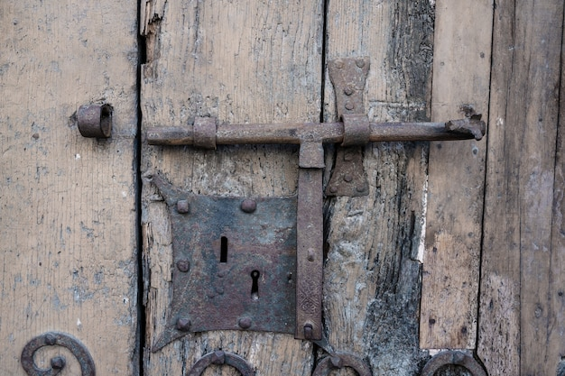 Detail of an old lock of a rusty door and with the old wood