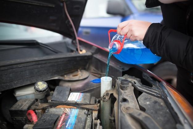 Деталь заливки жидкого стекла для защиты от замерзания в грязный автомобиль из сине-красного контейнера для воды с незамерзанием, концепция автомобиля