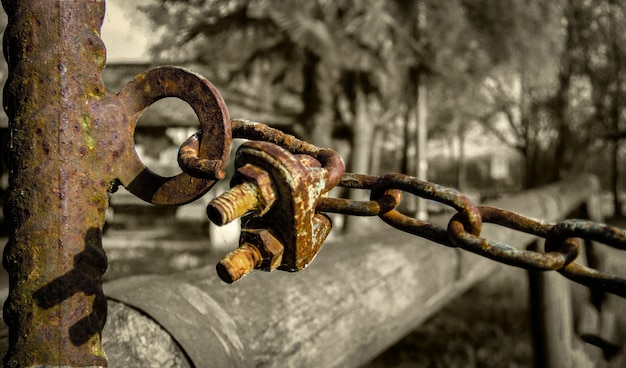 Detail of a rusty chain and a padlock and corroded by time in a situation with low very bleak and gloomy lighting. Premium Photo