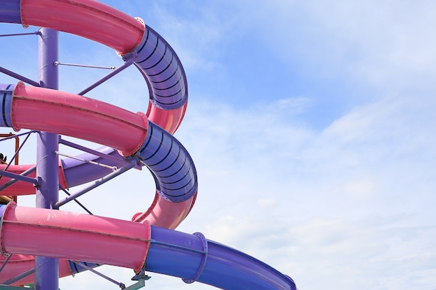 Detail of serpentines of the tubes of a water slide of swimming pool against sky background.