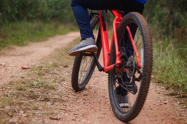 Detail shot of the feet of a young man riding his bike on a forest road, playing sports in nature.