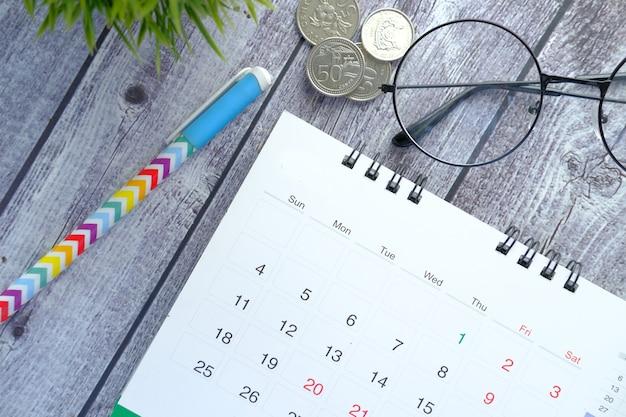 木製の机の上のカレンダーとペンの詳細ショット