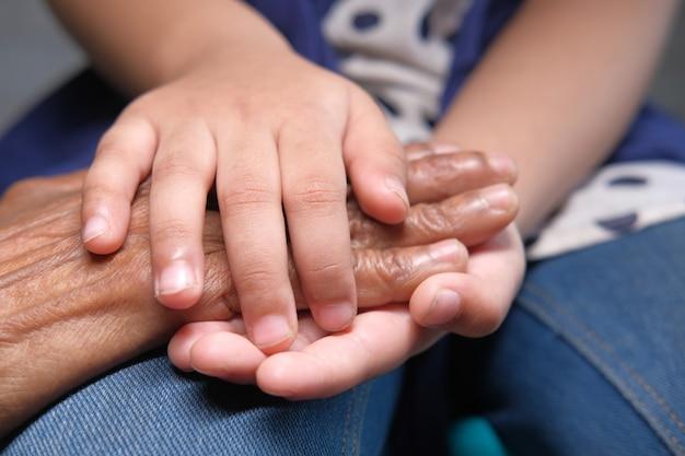 Детальный снимок ребенка, держащего за руку пожилых женщин,